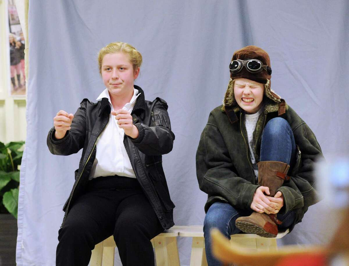 """Greenwich High School sophomores Nicole Wood, 16, left, and Flora Braes, 15, play pilots during a dress rehearsal performance titled """"Women Airforce Service Pilots & the Flight for Equality,"""" in the Greenwich High School Innovation Lab at the school in Greenwich on Friday. The production will be part of a national history competition these students will be participating in."""