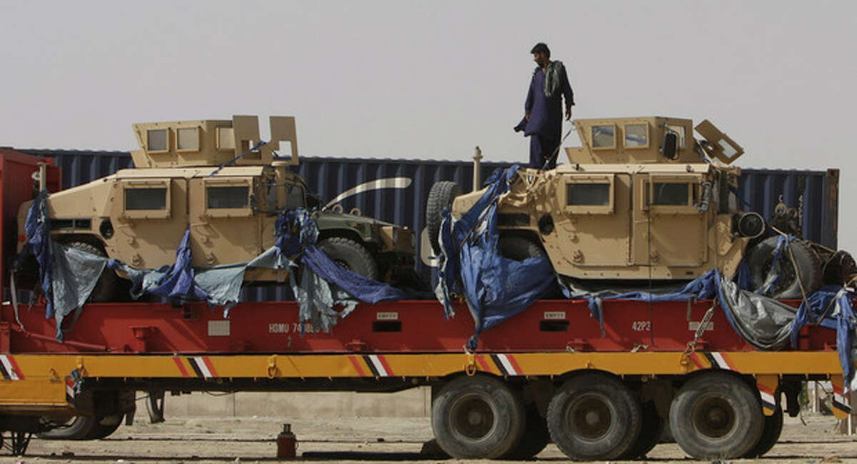 A driver stands on top of a truck carrying NATO Humvees at a terminal in the Pakistani-Afghan border, in Chaman, Pakistan, Wednesday, July 4, 2012. Trucks carrying NATO troop supplies are set to resume shipments to Afghanistan on Wednesday following a deal between the U.S. and Pakistan that ended Islamabad's seven-month blockade. (AP Photo/Matiullah Achakzai)