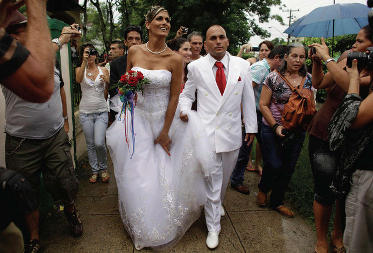Transsexual Wendy Iriepa and Ignacio Estrada leave the event hall where they were married in Havana, Cuba, Saturday Aug. 13, 2011. Iriepa, whose sex change operation was paid for by the state, tied the knot with Estrada in a first-of-its-kind wedding for Cuba. Gay marriage is not legal in Cuba and Saturday's wedding does nothing to change that since Iriepa is legally considered a woman. (AP Photo/Javier Galeano)