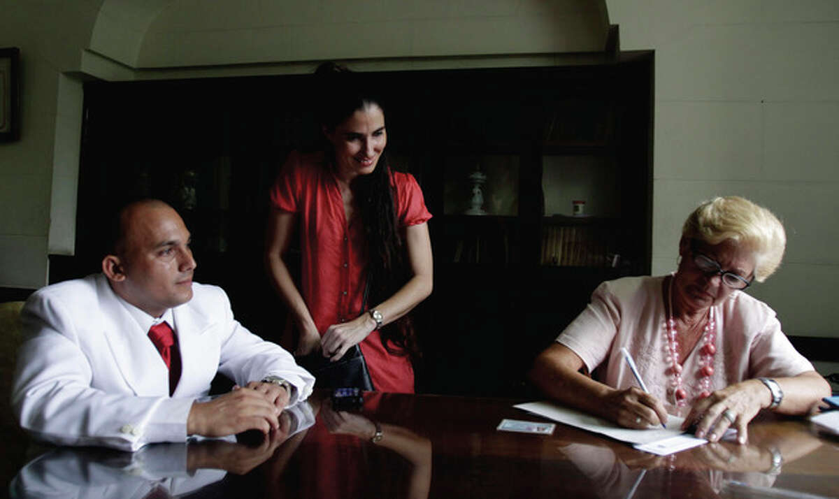Groom Ignacio Estrada, left, Cuba's blogger and maid of honor, Yoani Sanchez, center, and Cuba's notary Yolanda Morejon wait for the arrival of Estrada's bride, transsexual Wendy Iriepa, in Havana, Cuba, Saturday Aug.13, 2011. Iriepa, whose sex change operation was paid for by the state, tied the knot with Estrada in a first-of-its-kind wedding for Cuba. Gay marriage is not legal in Cuba and Saturday's wedding does nothing to change that since Iriepa is legally considered a woman. (AP Photo/Javier Galeano)