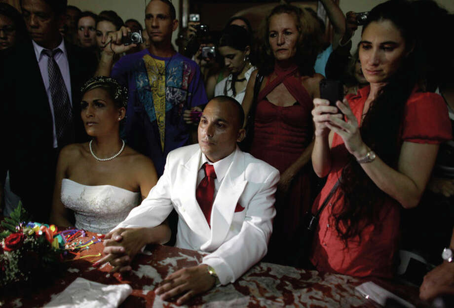 Cuba's blogger Yoani Sanchez and maid of honor, right, tweets during the wedding ceremony of transsexual Wendy Iriepa, left, and Ignacio Estrada, center, in Havana, Cuba, Saturday Aug. 13, 2011. Iriepa, whose sex change operation was paid for by the state, tied the knot with Estrada in a first-of-its-kind wedding for Cuba. Gay marriage is not legal in Cuba and Saturday's wedding does nothing to change that since Iriepa is legally considered a woman. (AP Photo/Javier Galeano) / AP