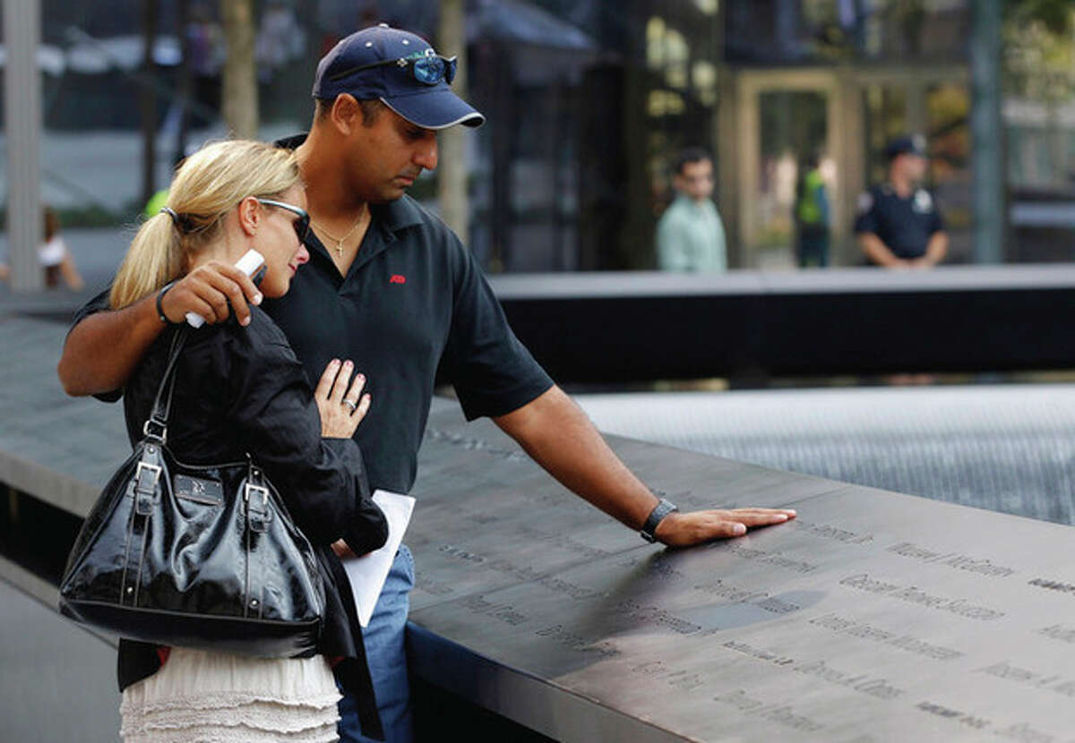 Visitors look over the names of victims etched into the wall on one of the pools at the 9/11 memorial plaza in the World Trade Center site in New York Monday, Sept. 12, 2011, on the first day that the memorial was opened to the public. (AP Photo/Mike Segar, Pool)