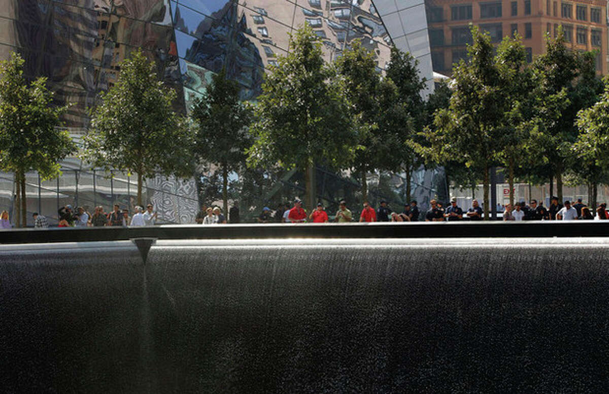 Visitors look over one of the pools at the 9/11 memorial plaza in the World Trade Center site in New York Monday, Sept. 12, 2011, on the first day that the memorial was opened to the public. (AP Photo/Mike Segar, Pool)