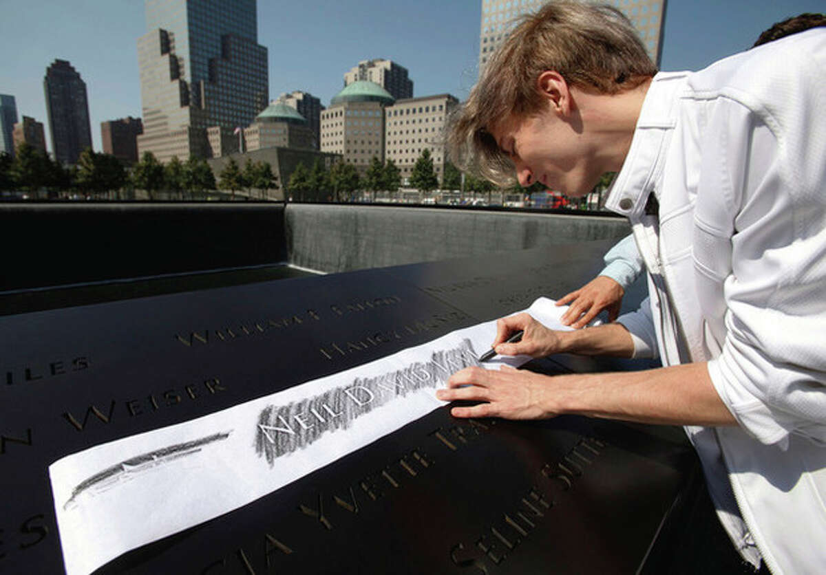 A visitor makes an etching of a victim's name inscribed on the wall surrounding one of the pools at the 9/11 memorial plaza in the World Trade Center site in New York Monday, Sept. 12, 2011, on the first day that the memorial was opened to the public. (AP Photo/Mike Segar, Pool)