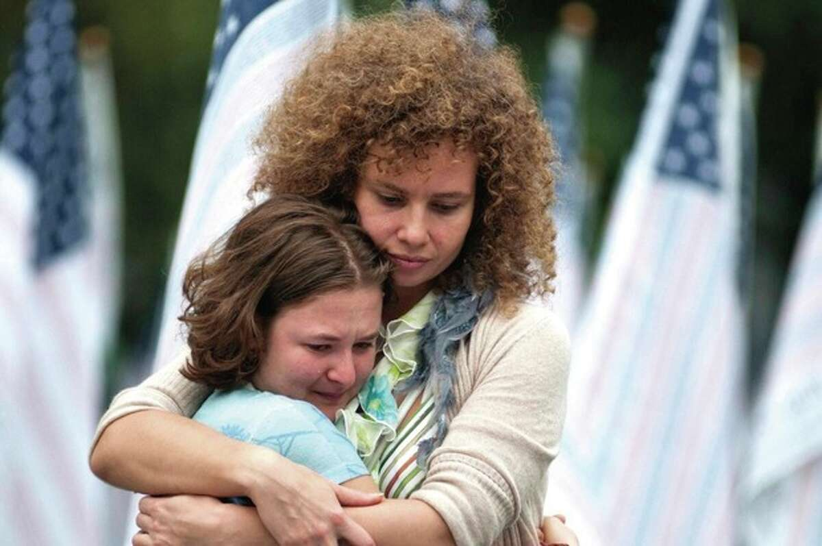 Miriam Love embraces her daughter at Battery Park in New York Sunday afternoon Sept. 11, 2011. Three thousand flags were placed in the park to honor those who were killed in the terrorist attacks on September 11, 2001. (AP Photo Allen Otto/The Daily Texan)