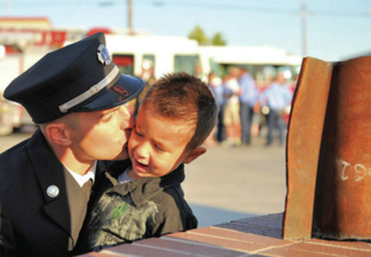 Capt. Frank Beauvais of the Nampa Fire Dept., gives his son Charlie, 4, a kiss on the cheek in front of a salvaged piece of steel that was found in the ruins of the World Trade Center and unveiled at a First Responders Ceremony on Sunday, September 11, 2011 at the Nampa Fire Station in Nampa, Idaho. (AP Photo/Idaho Press-Tribune, Adam Eschbach)