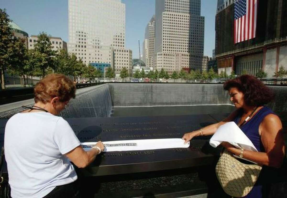 Katina Velahos, right, watches as Zoe Kousoulis makes a rubbing of the name of her daughter Danielle Kousoulis, who was killed in the 9/11 terrorist attacks, from one of the panels inscribed with the victims' names on the first day that the 9/11 memorial plaza was opened to the public at the World Trade Center site in New York, Monday, Sept. 12, 2011. (AP Photo/Mike Segar, Pool)