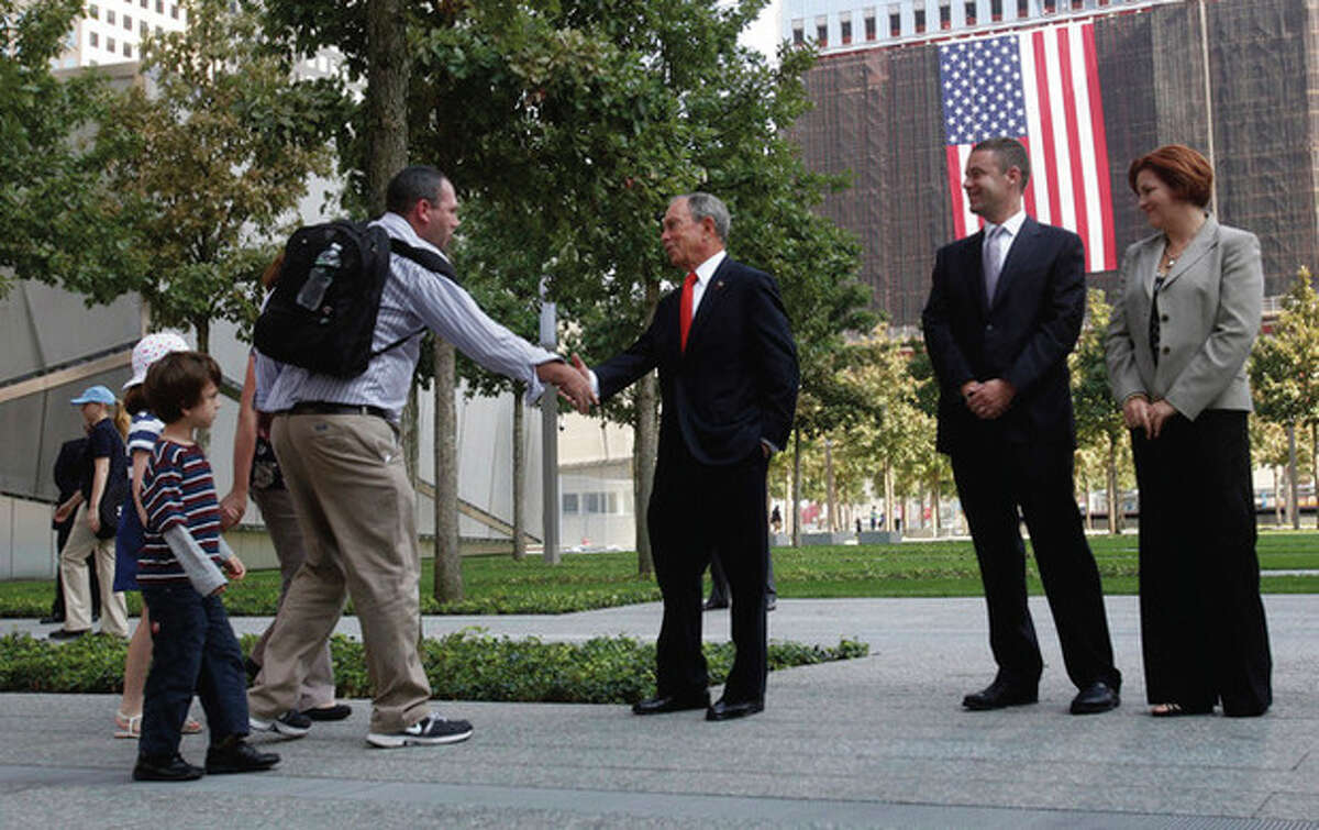 New York Mayor Michael Bloomberg, center, greets visitors to the 9/11 memorial plaza in the World Trade Center site in New York Monday, Sept. 12, 2011, on the first day that the memorial was opened to the public. (AP Photo/Mike Segar, Pool)