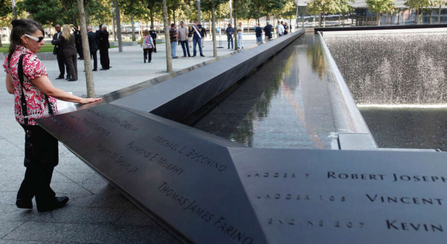 A visitor looks one of the pools at the 9/11 memorial plaza in the World Trade Center site in New York Monday, Sept. 12, 2011, on the first day that the memorial was opened to the public. (AP Photo/Mike Segar, Pool) / POOL Reuters