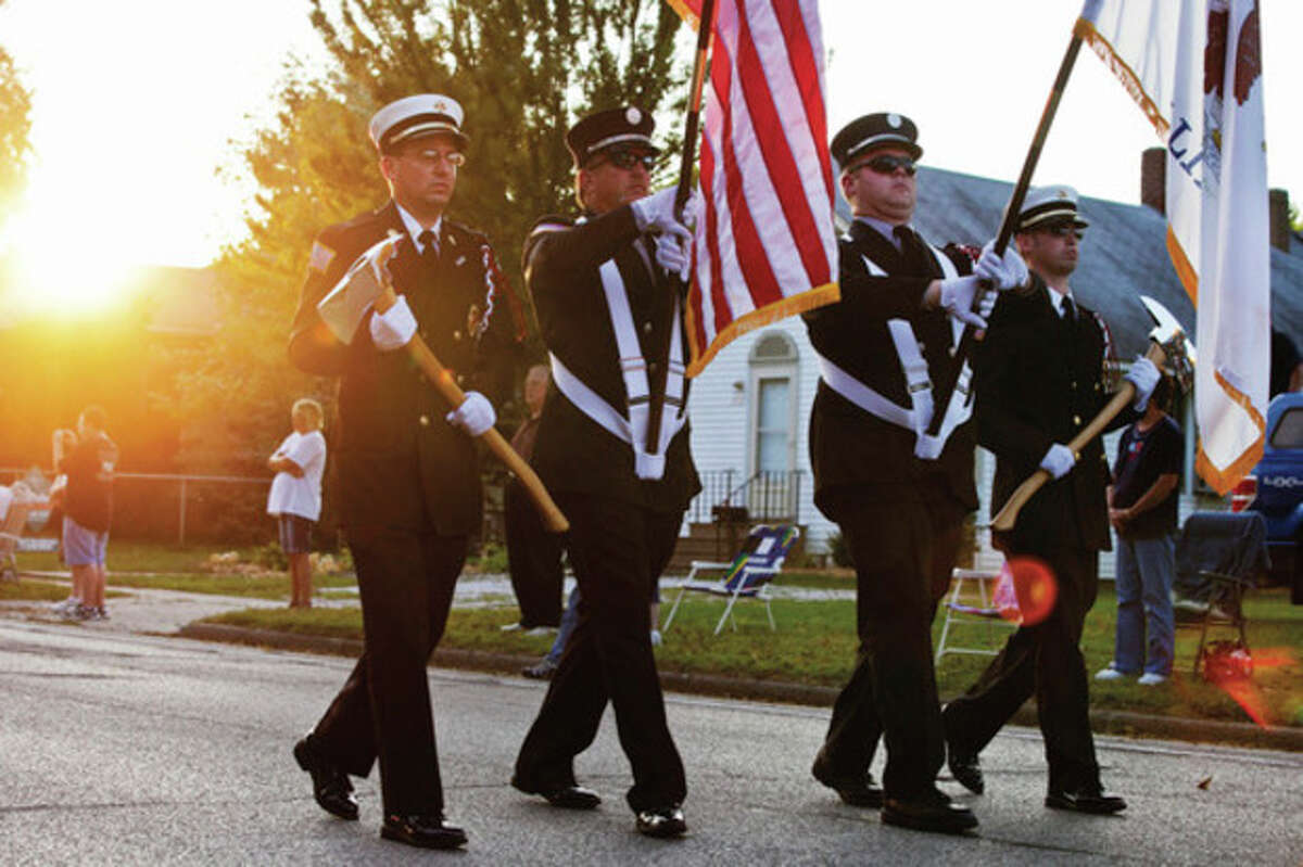 Henry, Ill. firefighters lead an emergency vehicle procession to Henry Central Park for a 9/11 memorial service on Sunday, Sept. 11, 2011, in Henry, Ill. An estimated 50 police, fire, and EMS departments were in attendance at the event. (AP Photo/Eve Edelheit/Peoria Journal Star)