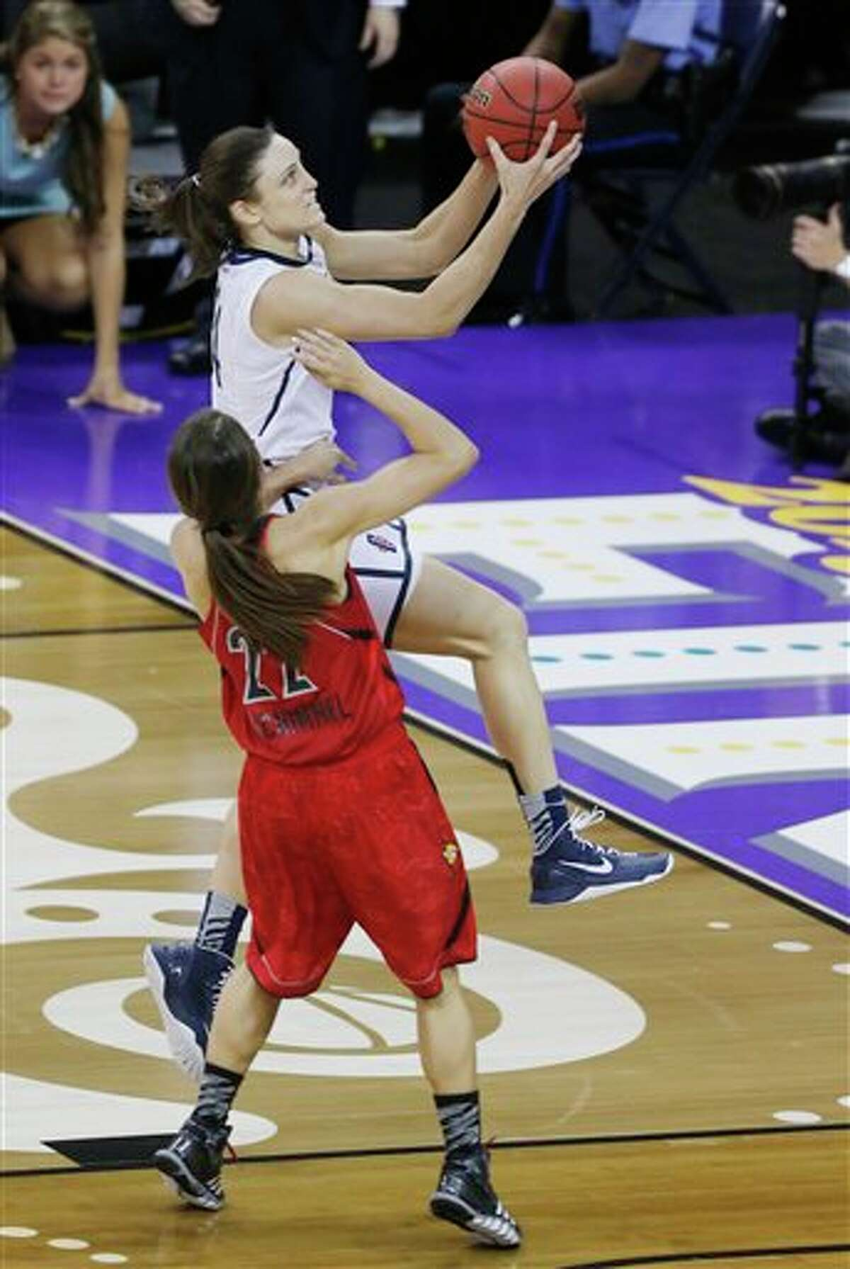 Connecticut guard Kelly Faris (34) goes up for a shot against Louisville guard Jude Schimmel (22) during the second half of the national championship game of the women's Final Four of the NCAA college basketball tournament, Tuesday, April 9, 2013, in New Orleans. (AP Photo/Bill Haber)