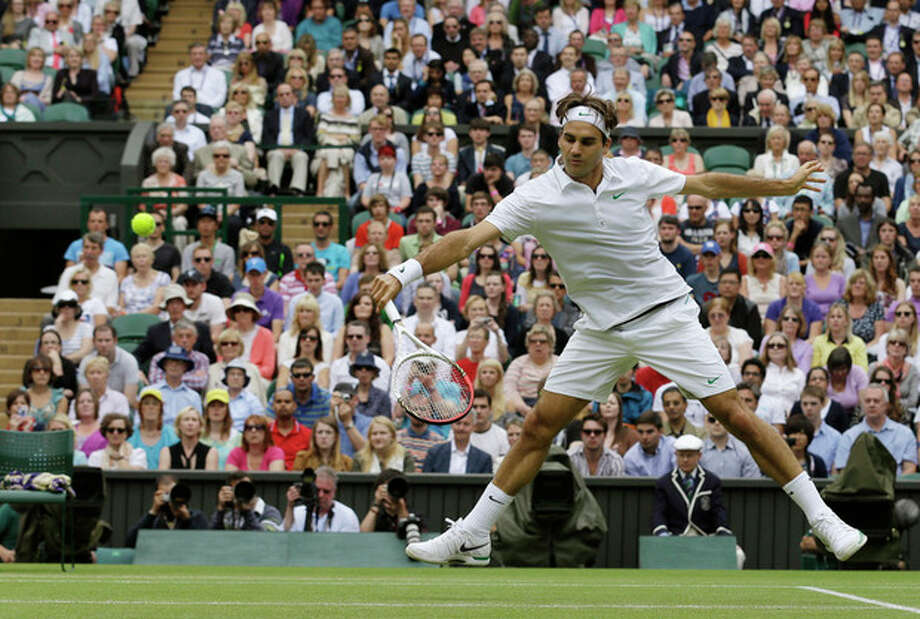 Roger Federer of Switzerland plays a return to Mikhail Youzhny of Russia during a quarterfinals match at the All England Lawn Tennis Championships at Wimbledon, England, Wednesday July 4, 2012. (AP Photo/Anja Niedringhaus) / AP