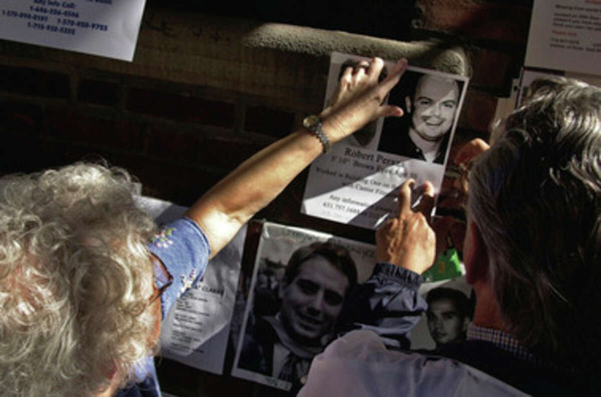 In this photo of Sept. 16, 2001, Robert and Suzanne Peraza place a flyer about their son Robert David Peraza on a wall in New York. Robert David Peraza was on the 104th floor of tower 1 of the World Trade Center when it was hit by the first hijacked airplane during a terrorist attack Tuesday, Sept. 11, 2001. In a widely published photo, Robert Peraza is shown kneeling at the September 11 Memorial during the 10th anniversary ceremony, Sunday, Sept. 11, 2011. (AP Photo/The Cincinnati Enquirer, Craig Ruttle) MANDATORY CREDIT; NO SALES