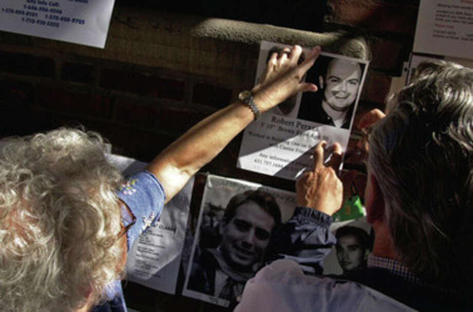 In this photo of Sept. 16, 2001, Robert and Suzanne Peraza place a flyer about their son Robert David Peraza on a wall in New York. Robert David Peraza was on the 104th floor of tower 1 of the World Trade Center when it was hit by the first hijacked airplane during a terrorist attack Tuesday, Sept. 11, 2001. In a widely published photo, Robert Peraza is shown kneeling at the September 11 Memorial during the 10th anniversary ceremony, Sunday, Sept. 11, 2011. (AP Photo/The Cincinnati Enquirer, Craig Ruttle) MANDATORY CREDIT; NO SALES / Cincinnati Inquirer