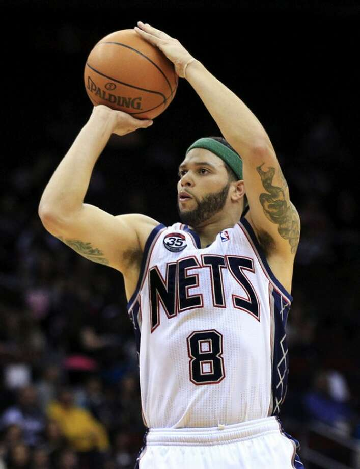"""FILE - In this April 6, 2012, file photo, New Jersey Nets' Deron Williams (8) shoots during the first half of an NBA basketball game against the Washington Wizards in Newark, N.J. Williams said on his Twitter page, Tuesday, July 3, that he """"made a very tough decision today"""" and posted a picture of the new team logo that accompanies the Nets' move from New Jersey to Brooklyn. A person with knowledge of the decision says Williams told the team Tuesday he was accepting their five-year contract worth $98 million. (AP Photo/Mel Evans, File)"""