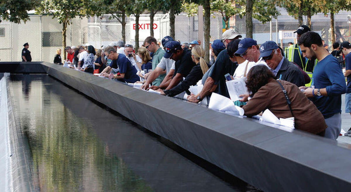 Visitors make etchings of the names of victims inscribed on the wall surrounding one of the pools at the 9/11 memorial plaza in the World Trade Center site in New York Monday, Sept. 12, 2011, on the first day that the memorial was opened to the public. (AP Photo/Mike Segar, Pool)
