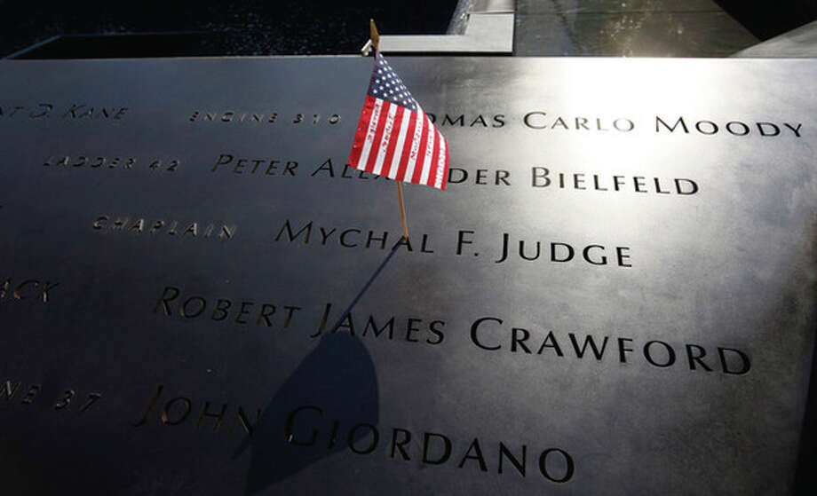 An American flag is stuck into the etched name of Father Mychal F. Judge, the New York Fire Department chaplain who died in the 9/11 attacks on the World Trade Center, at the National September 11 Memorial in New York Monday, Sept. 12, 2011. The 9/11 memorial plaza opened to the public Monday for the first time. (AP Photo/Mike Segar, Pool) / POOL Reuters