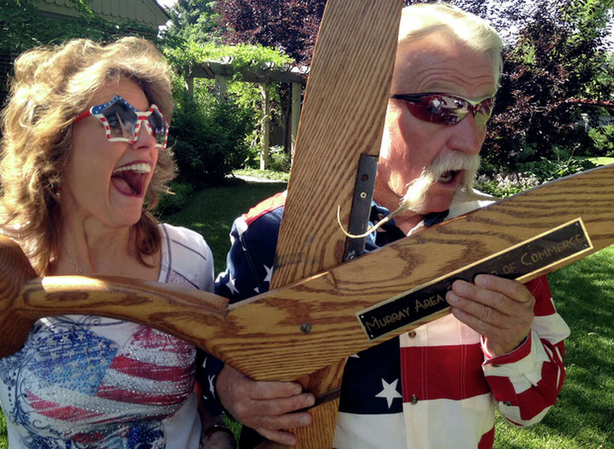 In this photo provided by Trevor Snarr, Dan Snarr, the mayor of the Salt Lake City suburb of Murray, jokes with wife, April, on Wednesday, July, 4, 2012, in Murray, Utah, after a parade in which he put all 18 inches of his handlebar mustache up for a vote. He has been growing it for 31 months but says he will shave if a majority of residents voted thumbs-down during the annual parade. (AP Photo/Courtesy Trevor Snarr)