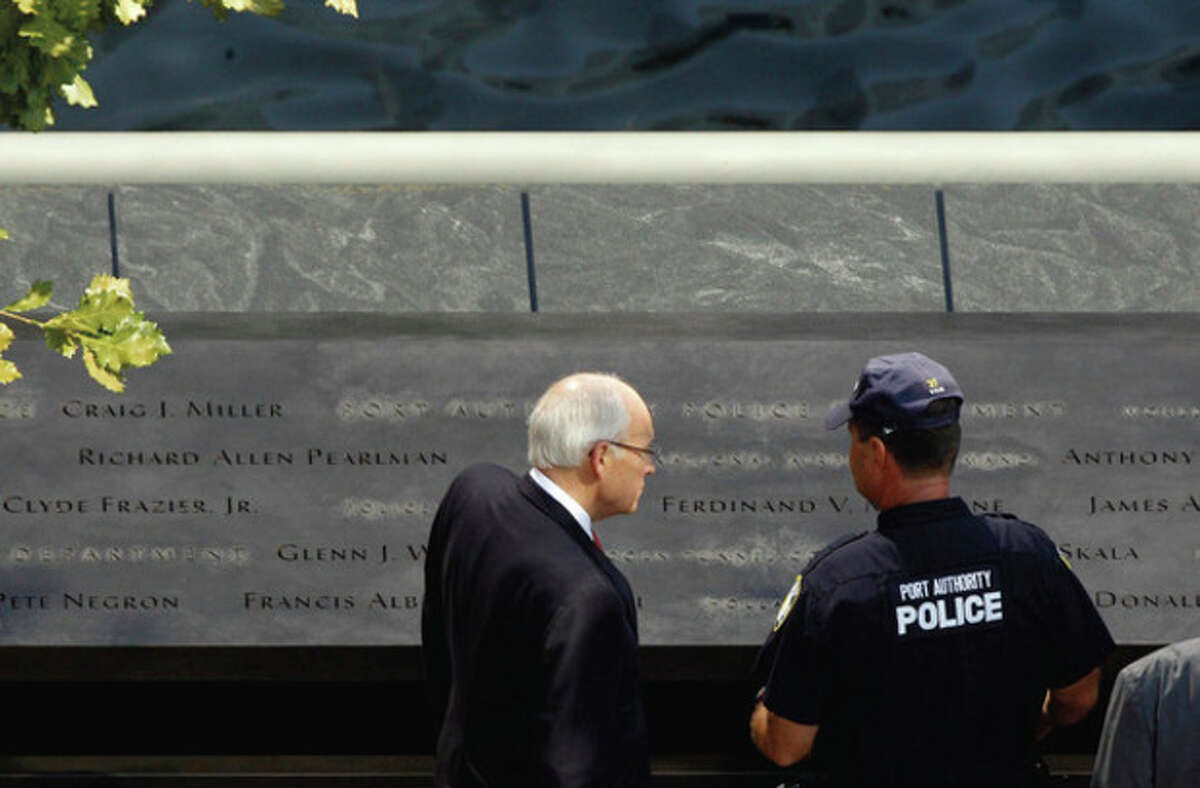 Former Vice President Dick Cheney, left, pauses by a bronze plaque inscribed with the names of the victims of the Sept. 11 terror attacks, during a tour of the National September 11 Memorial, Monday, Sept. 12, 2011, in New York. (AP Photo/Matt Rourke)