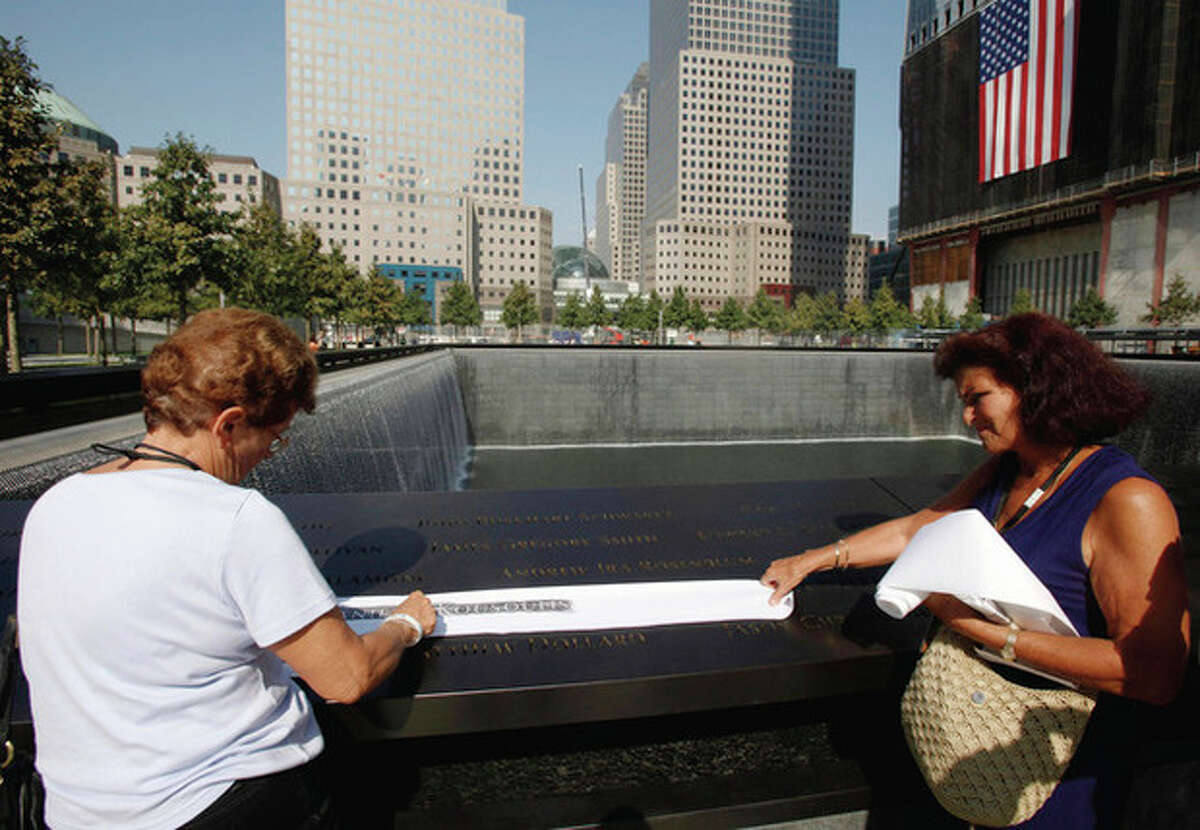 Visitors make an etching of victim's name inscribed on the wall surrounding one of the pools at the 9/11 memorial plaza in the World Trade Center site in New York Monday, Sept. 12, 2011, on the first day that the memorial was opened to the public. (AP Photo/Mike Segar, Pool)