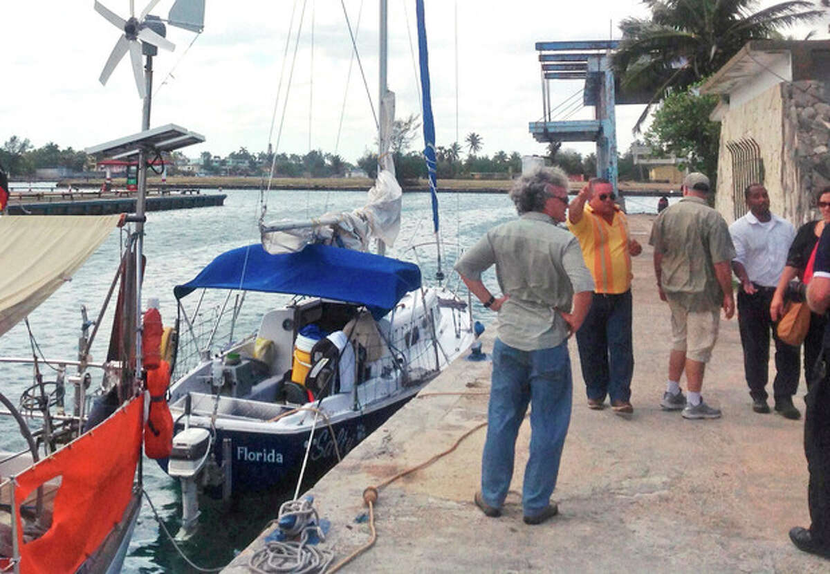 A state security officer, in yellow, instructs journalists to stop making pictures of Joshua Hakken's blue sailboat, Salty, docked at the Hemingway Marina, in Havana, Cuba, Tuesday, April 9, 2013. Hakken and his wife Sharyn, who had lost custody of their two young boys, allegedly kidnapped them from Sharyn's parents and fled by boat to Havana. A foreign ministry official told The Associated Press in a written statement Tuesday that Cuba had informed U.S. authorities of the country's decision to turn over Hakken, his wife and their two young boys. She did not say when the handover would occur. (AP Photo/Peter Orsi)