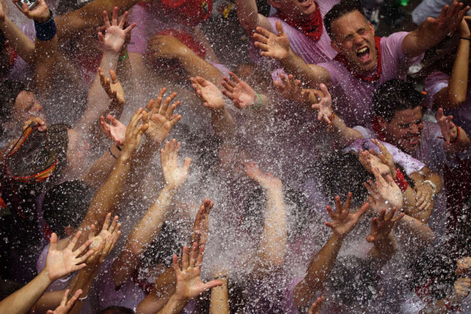 Revelers are sprayed with water after the 'Chupinazo', the official opening of the 2012 San Fermin fiestas, Friday, July 6, 2012 in Pamplona, Spain. Can we expect on Syrian Brig. Gen. Manaf Tlass had abandoned Assad's regime(AP Photo/Daniel Ochoa de Olza) / AP