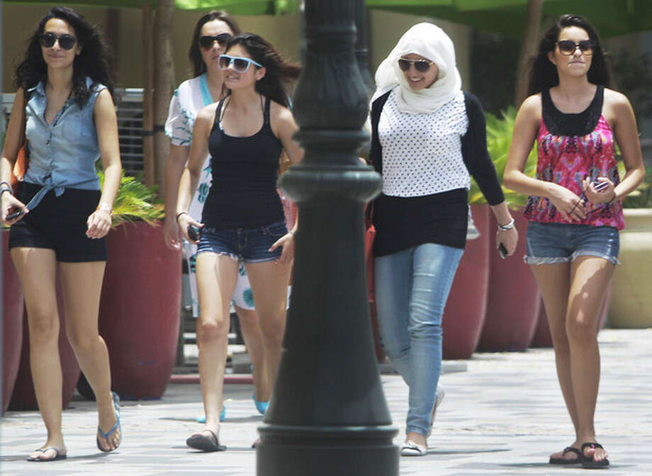 In this photo taken Saturday, June 23, 2012, Women of different nationalities walk at the Jumeirah Beach Residence Walk in Dubai , United Arab Emirates. As the numbers of foreigners have increased, so have the stories of them violating the UAE's strict indecency code which limits drinking to bars and nightclubs and bans public displays of affection. (AP Photo/Kamran Jebreili) / AP