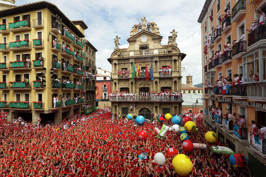Revelers hold up traditional red neckties during the 'Chupinazo', the official opening of the 2012 San Fermin fiestas, Friday, July 6, 2012 in Pamplona, Spain. Revelers from around the world kick off the San Fermin festival with a messy party in the Pamplona town square, one day before the first of eight days of the running of the bulls. (AP Photo/Daniel Ochoa de Olza) / AP