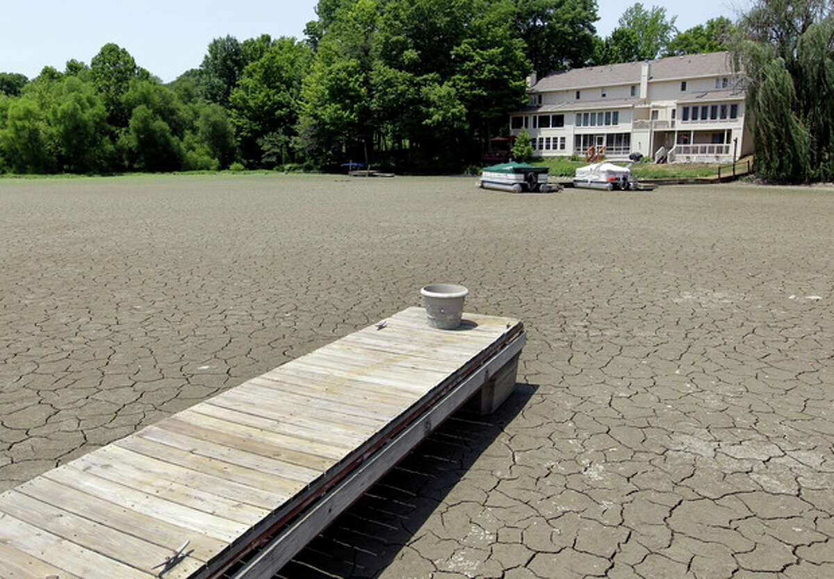 A dock extends into a dry cove at Morse Reservoir in Noblesville, Ind., Thursday, July 5, 2012. The reservoir is down 3.5 feet from normal levels. Oppressive heat is slamming the middle of the country with record temperatures that aren't going away after the sun goes down. Temperatures exceeded 100 degrees in Central Indiana. (AP Photo/Michael Conroy)