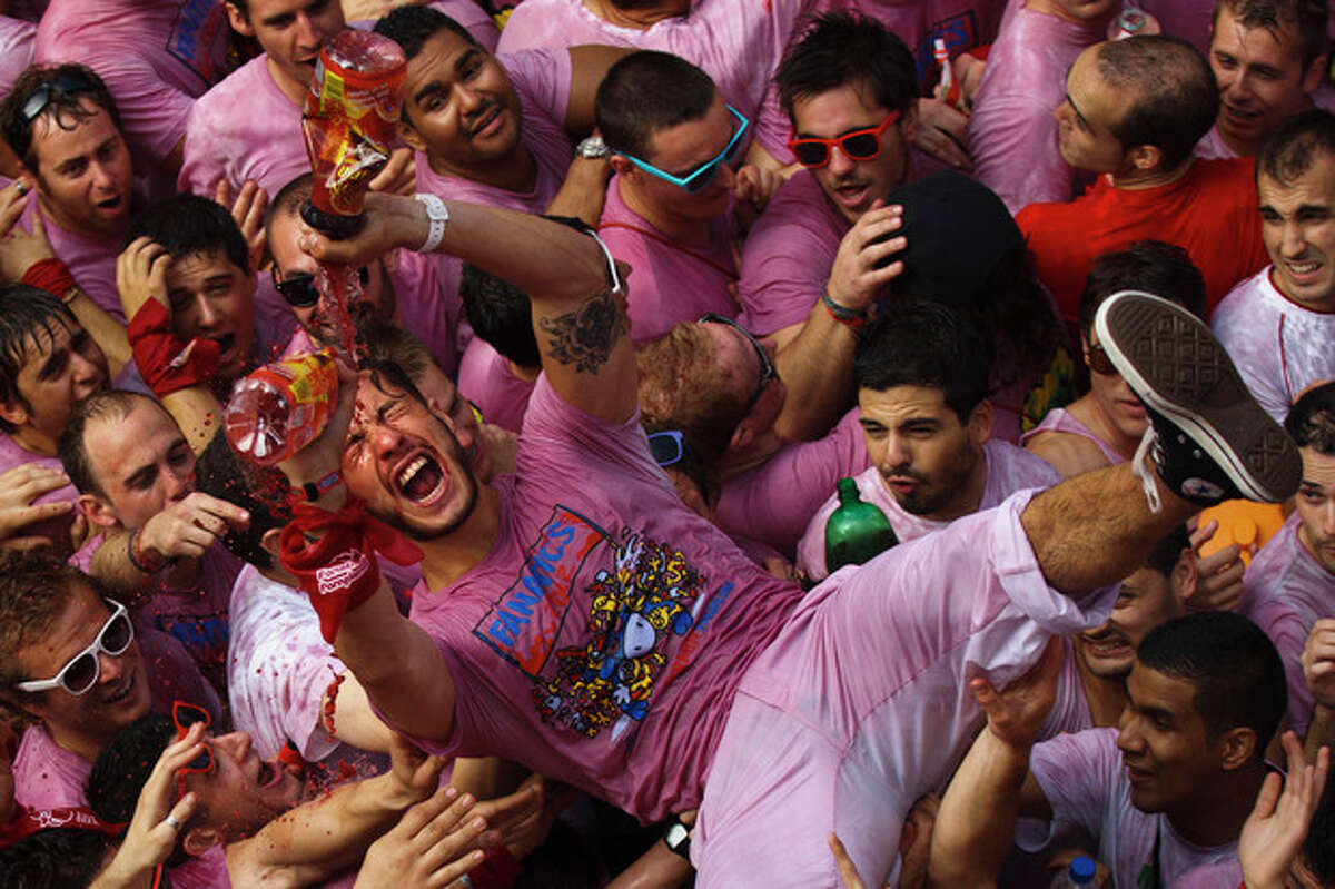 A reveler drinks wine during the 'Chupinazo', the official opening of the 2012 San Fermin fiestas, Friday, July 6, 2012 in Pamplona, Spain. Can we expect on Syrian Brig. Gen. Manaf Tlass had abandoned Assad's regime(AP Photo/Daniel Ochoa de Olza)
