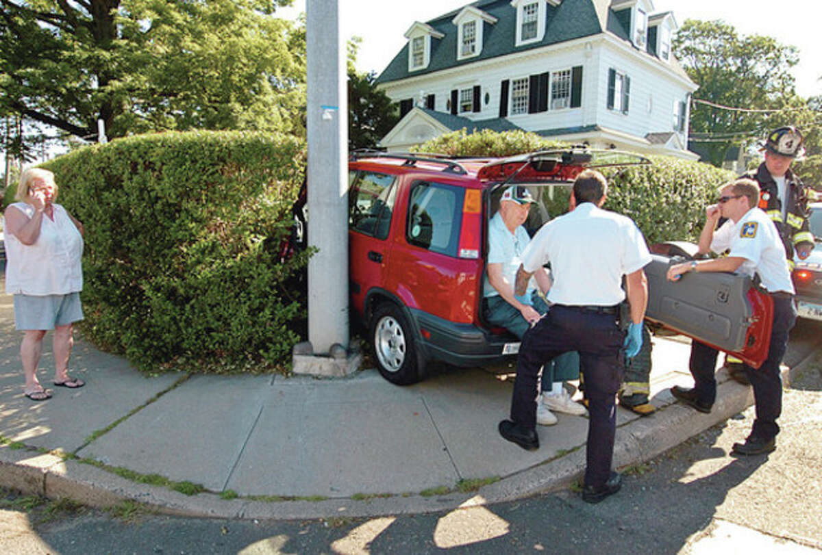 Norwalk emergency personnel interview a driver involved in a two car accident on East Ave who drove his car through a hedge at the corner of Morgan Ave. Hour photo / Erik Trautmann