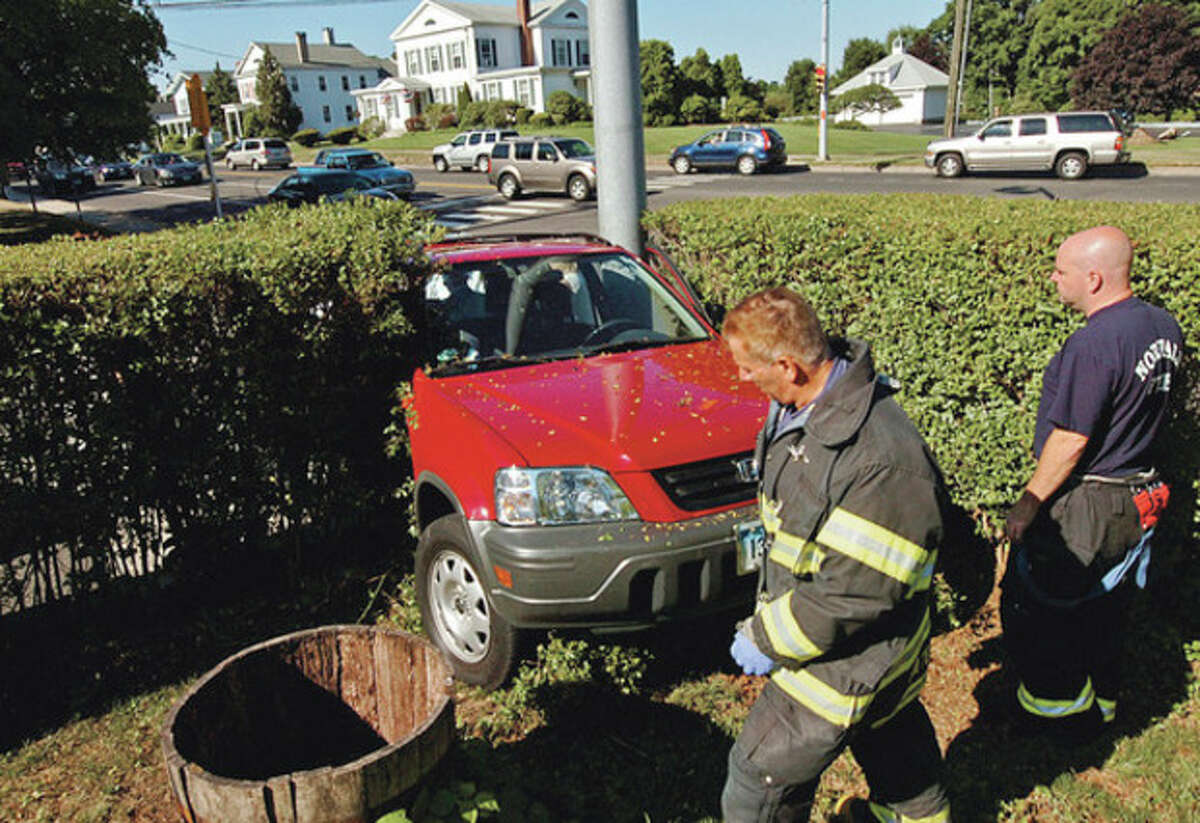 Norwalk emergency personnel investigate a two car accident on East Ave which resulted in one of the cars driving through a hedge at the corner of Morgan Ave. Hour photo / Erik Trautmann