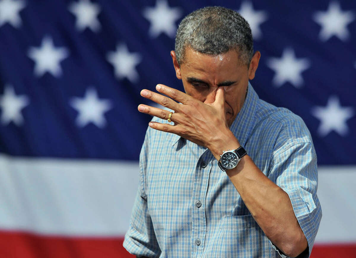 President Barack Obama wipes sweat from his eye after a speech at Washington Park in Sandusky, Ohio, Thursday, July 5, 2012. Obama is on a two-day bus trip through Ohio and Pennsylvania. (AP Photo/David Richard)