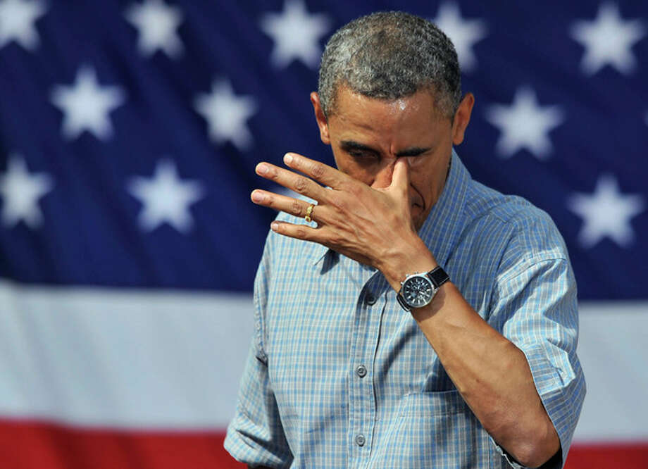 President Barack Obama wipes sweat from his eye after a speech at Washington Park in Sandusky, Ohio, Thursday, July 5, 2012. Obama is on a two-day bus trip through Ohio and Pennsylvania. (AP Photo/David Richard) / FR25496 AP
