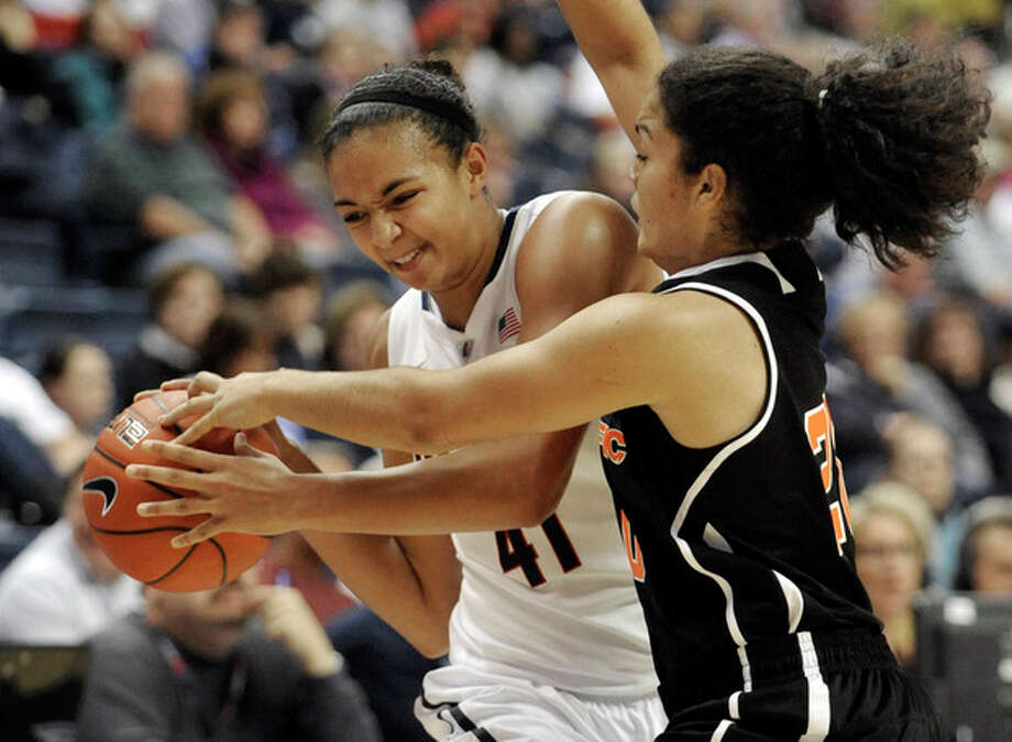 Connecticut's Kiah Stokes, left, is pressured by Pacific's Brianna Johnson during the first half of an NCAA college basketball game Storrs, Conn., Tuesday, Nov. 15, 2011. (AP Photo/Jessica Hill) / AP2011