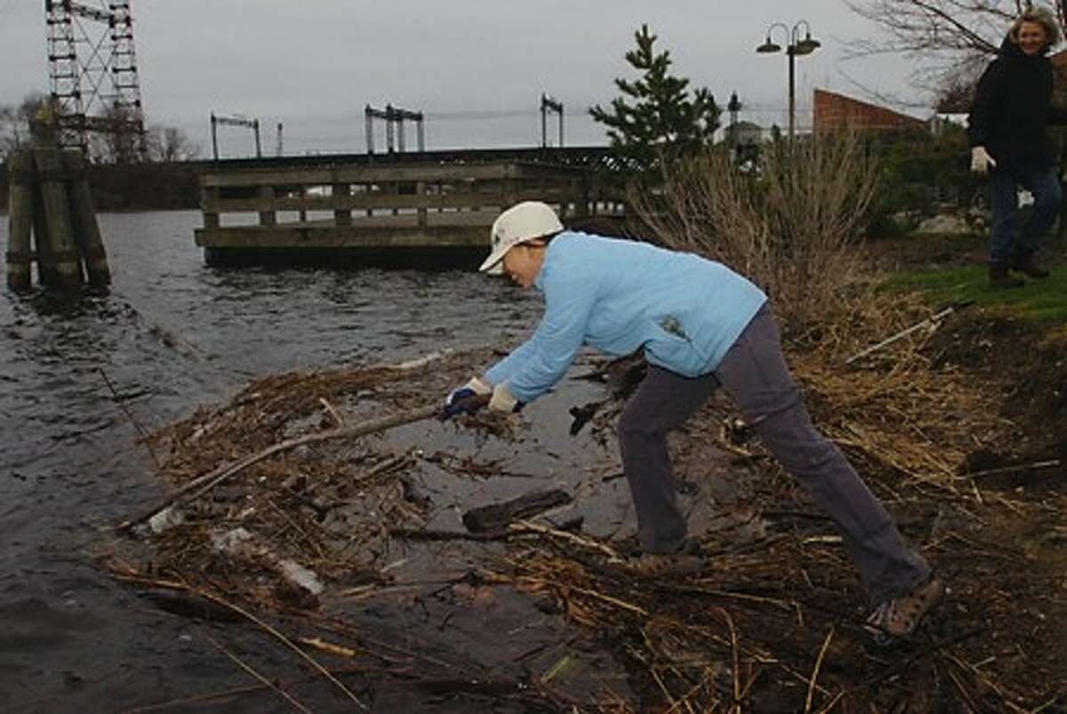 Cherry Tunsmith reaches for garbage floating in the Norwalk River as she volunteers for the Norwalk River Watershed Association Clean Up Saturday. Hour photo / Erik Trautmann