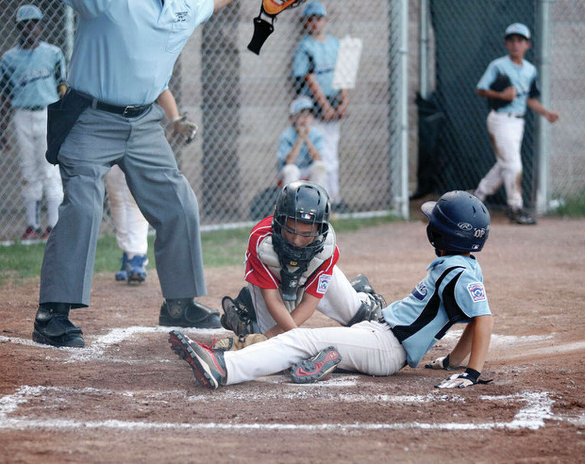 Norwalk's #33, Shane Popkins, makes a play at home plate during a U-10 Little League District 1 semifinal game against Wilton at Scalzi Park in Stamford Thursday evening. Hour Photo / Danielle Robinson