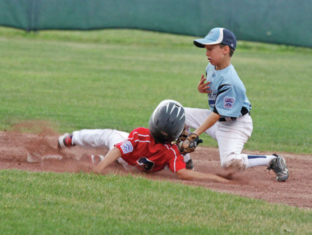 Hour photos / Danielle Robinson Above, Norwalk's Michael Boyian slides into Wilton second baseman Will Gioffre during a U-10 Little League District 1 semifinal game Thursday at Scalzi Park in Stamford. Below left, Norwalk's Shane Popkins makes a play at home plate. Below right, Boyian tosses a strike.