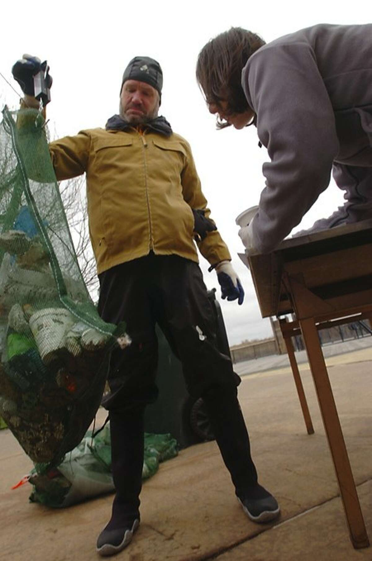 David park weighs garbage he pulled from the Norwalk River as Sara Dasilva of the Norwalk River Watershed Association Clean notes the weight during the Association''s annual clean up Saturday. Hour photo / Erik Trautmann