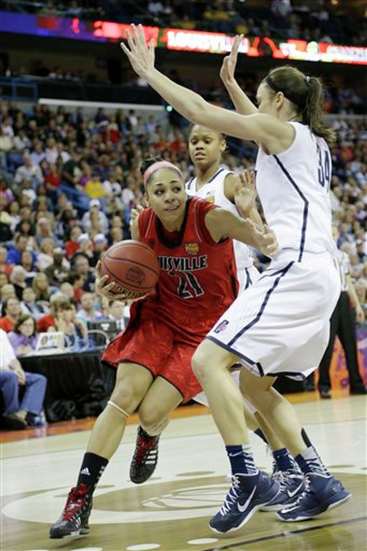 Louisville guard Bria Smith (21) drives the ball against Connecticut guard Kelly Faris (34) during first half of the national championship game of the women's Final Four of the NCAA college basketball tournament, Tuesday, April 9, 2013, in New Orleans. (AP Photo/Gerald Herbert)