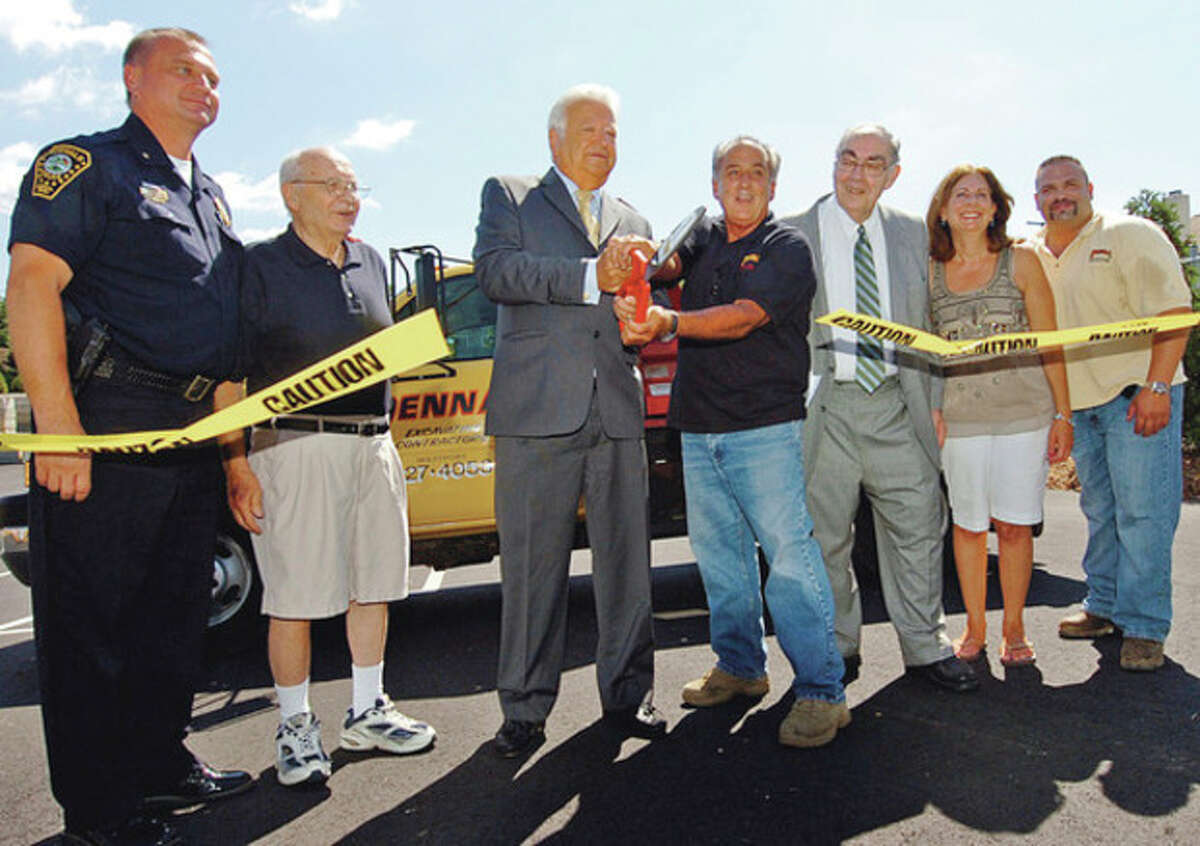 Interim Police Chief Thomas Kuhalwik, former mayor Frank Esposito, mayor Richard Moccia, Vinny Penna, attorney Frank Zullo, Robin Penna, and Jason Penna cut the ribbon at the Penna's new construction yard on Goldstein Place in Norwalk, during a ribbon cutting ceremony Friday. Hour photo / Erik Trautmann