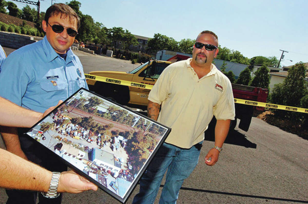 Firefighter Kosmas Kalmanidis and Jason Penna of Penna Construction, whose company opened a new construction yard on Goldstein Place in Norwalk, look an an ariel photo of the blighted junk yard that preceded them, during a ribbon cutting ceremony Friday. Hour photo / Erik Trautmann