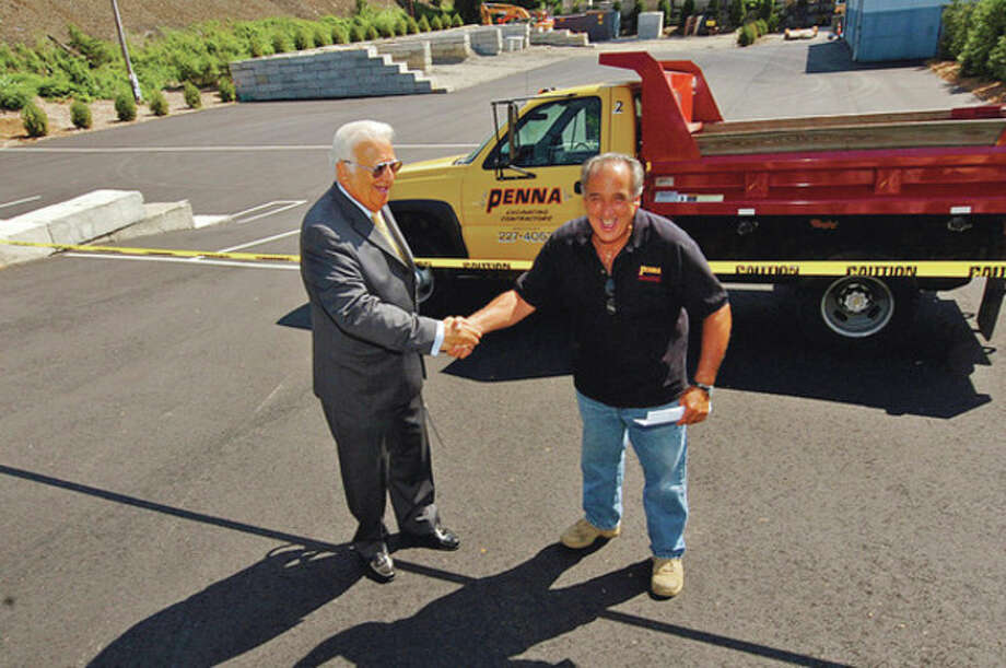 Hour photo / Erik TrautmannMayor Richard Moccia greets Vinny Penna, owner of A.J. Penna Construction, which opened a new construction yard on Goldstein Place in Norwalk during a ribbon cutting ceremony Friday. / (C)2012, The Hour Newspapers, all rights reserved