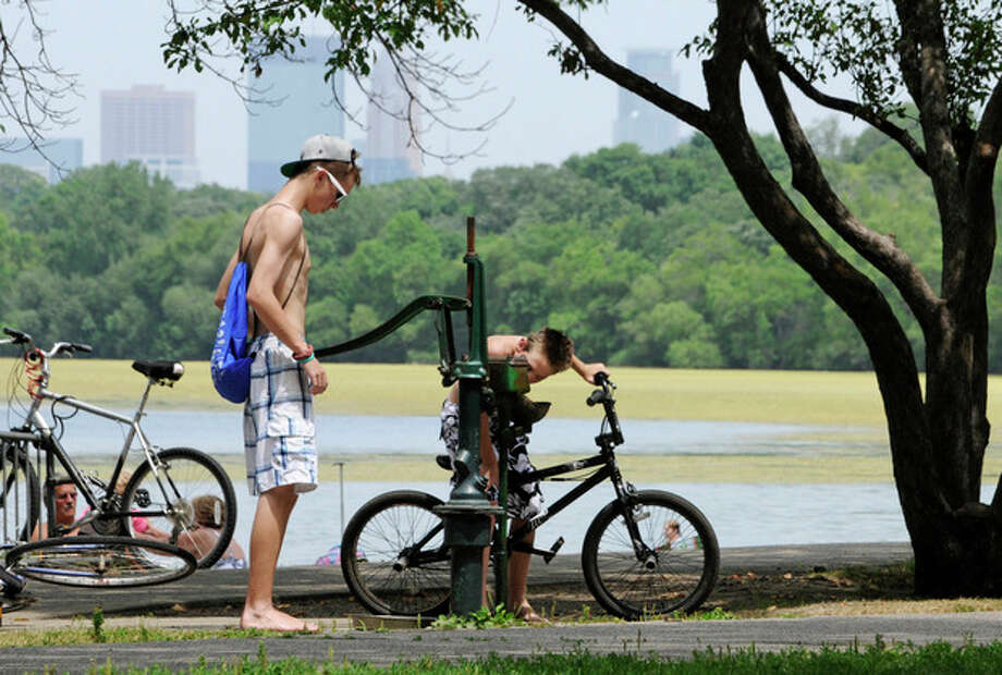 The skyline rises through haze as one boy pumps water for another to drink from an old-fashioned water pump along Lake Harriet Friday, July 6, 2012 in Minneapolis where temperatures reached into the upper 90's for another day during the heat wave. The National Weather Service said the record-breaking heat that has baked the nation's midsection for several days was slowly moving into the mid-Atlantic states and Northeast. Excessive-heat warnings remained in place Friday for all of Iowa, Indiana and Illinois as well as much of Wisconsin, Michigan, Missouri, Ohio and Kentucky. (AP Photo/Jim Mone) / AP