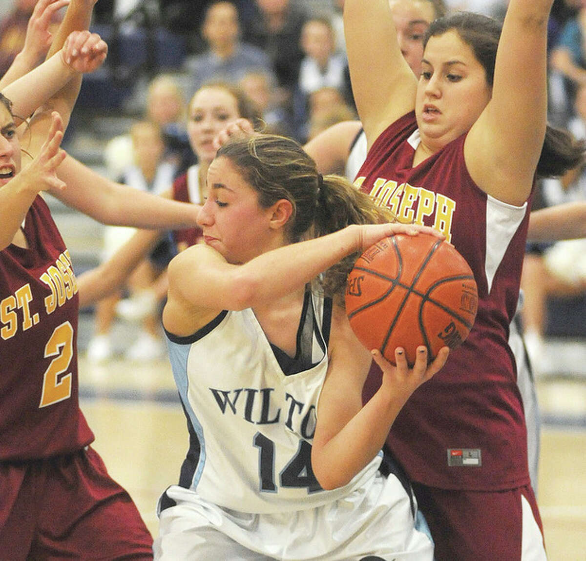 Hour Photo/John Nash - Wilton's Alyssa Malvarosa finds herself surrounded by St. Joseph players as she protects the ball after grabbing an offensive rebound during the second half of Tuesday's game.