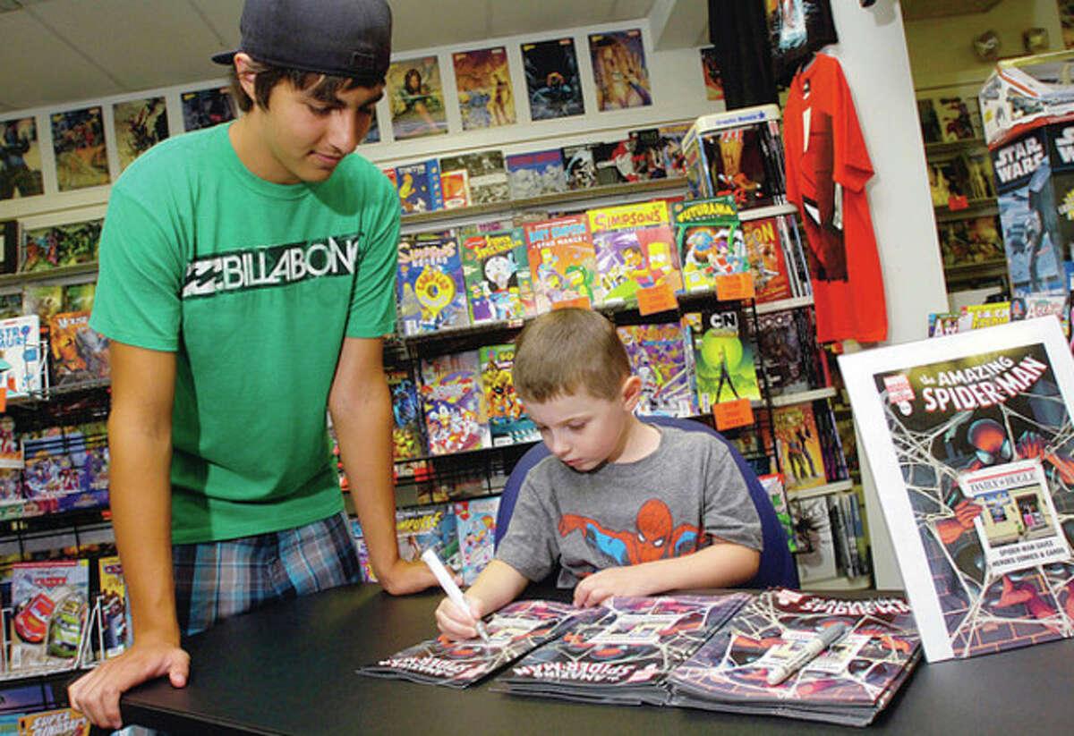 "Hour photos / Erik Trautmann Ben Kruseski signs a copy of ?'The Amazing Spider-Man #666?"" for his cousin, Christian Soto."