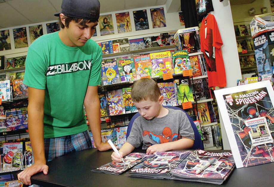 Hour photos / Erik Trautmann Ben Kruseski signs a copy of ÒThe Amazing Spider-Man #666Ó for his cousin, Christian Soto. / (C)2011, The Hour Newspapers, all rights reserved