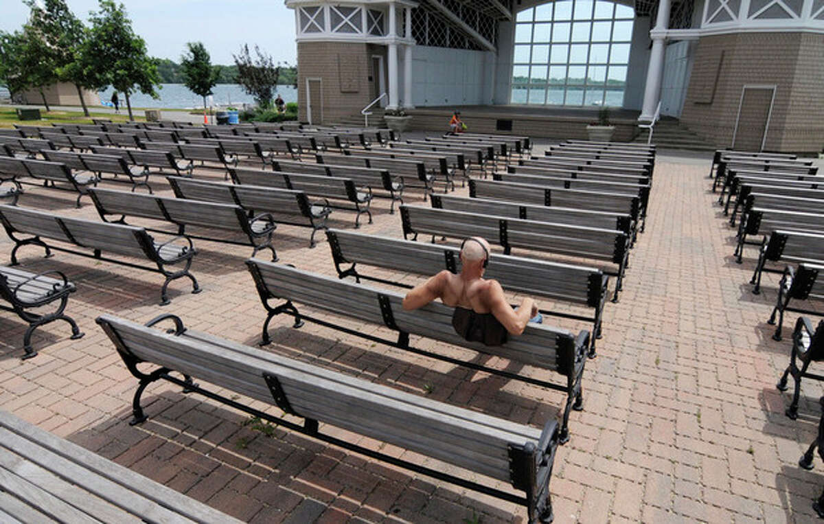 A man has the Lake Harriet Bandshell seats to himself Friday, July 6, 2012 in Minneapolis where temperatures reached into the upper 90's for another day during the heat wave. The National Weather Service said the record-breaking heat that has baked the nation's midsection for several days was slowly moving into the mid-Atlantic states and Northeast. (AP Photo/Jim Mone)