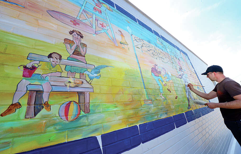 Artist Ziggy Bober paints a mural at Calf Pasture Beach Tuesday as warm weather finally hits the area. Hour photo / Erik Trautmann / (C)2013, The Hour Newspapers, all rights reserved
