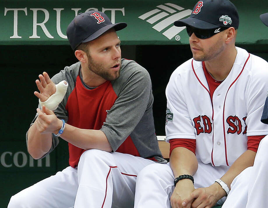 Boston Red Sox's Dustin Pedroia gestures with his bandaged hand as he chats with Cody Ross, right, during the first baseball game of a day-night doubleheader against the New York Yankees at Fenway Park in Boston, Saturday, July 7, 2012. Pedroia is on the 15-day disabled list (retroactive to July 4) with a right thumb sprain. (AP Photo/Elise Amendola) / AP